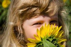 De ruikende zonnebloem van het meisje Stock Fotografie