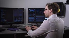 De ruimte met computers De man die de speciale software gebruiken probeert om belangrijke informatie te vinden De persoon een wit stock footage