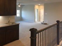 De ruimte van de eerste verdiepingfamilie in nieuw huis stock afbeelding