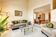 De ruimte van de luxefamilie in zachte romige tonen en esdoorneettafel s Stock Afbeelding