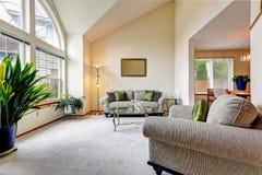 De ruimte van de luxefamilie in zachte romige tonen met hoogteplafond en a Stock Foto