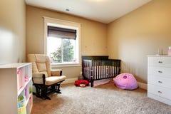 De ruimte van de verzorging voor babymeisje met bruine houten voederbak. stock fotografie