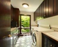 De ruimte van de wasserij met houten kabinetten en witte wasmachine en droger. Stock Foto