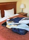 De ruimte van het hotel met koffer en kleren stock afbeeldingen