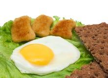 De ruimte van het ontbijtexemplaar: gebraden ei, sla, kernachtig brood en goudklompje stock foto