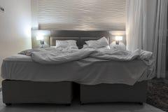 De ruimte van het tweepersoonsbedhotel met het geknoeide licht van de bednacht Stock Foto