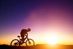 De ruiter van de bergfiets op de heuvel met zonsopgang Stock Foto
