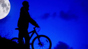 De ruiter van de fietsnacht gaat in maanlicht naar huis stock videobeelden