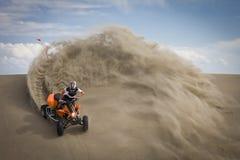 De ruiter van de vierling in de zitstok van zandduinen Royalty-vrije Stock Fotografie
