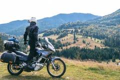 De ruitermens kijkt aan afstand op zijn toeristische motorfiets, met grote zakken klaar voor een lange reis, zwarte stijl, witte  stock afbeeldingen