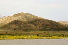 De ruiters op horseback berijden bij de voet van de berg op de prairies stock afbeelding