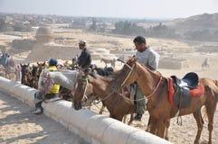 De Ruiters van het paard rond de Piramides Stock Foto's