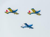 De rumänska hökarna Team piloter med deras kulöra flygplan som utbildar i den blåa himlen royaltyfri bild