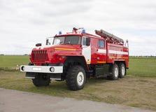 De Russische brandvrachtwagen van rode kleur met intrekbare ladders bevindt zich op het vliegveld stock foto's