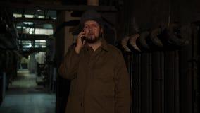 De Russische mens in een hoed met earflaps, die op de telefoon in een donkere kelderverdieping spreken en beslist kwesties van na stock video