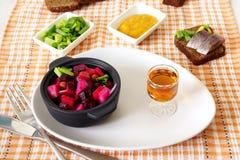 De Russische vinaigrette van de bietensalade en een glas brandewijn stock afbeelding