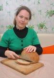 De Russische vrouw snijdt eigengemaakt brood in de keuken Royalty-vrije Stock Foto's