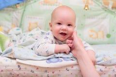 De rust van de baby op bed en bekijkt camera Royalty-vrije Stock Afbeelding