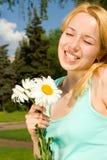 De rust van de vrouw in het park met bloemen Stock Afbeeldingen