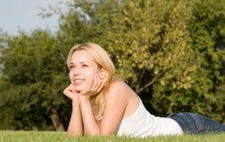 De rust van de vrouw op het gras Royalty-vrije Stock Fotografie