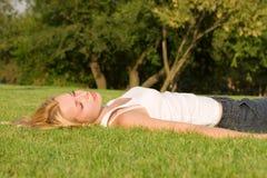 De rust van de vrouw op het gras Stock Foto's