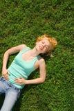 De rust van de vrouw op het gras Royalty-vrije Stock Afbeeldingen
