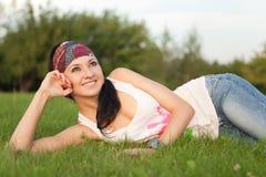 De rust van de vrouw op het groene gras Royalty-vrije Stock Foto
