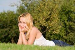 De rust van de vrouw op het groene gras Stock Foto