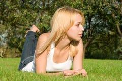 De rust van de vrouw op het groene gras Stock Afbeeldingen