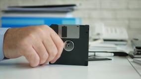 De rusteloze zakenman die ter beschikking een diskette houden maakt zenuwachtige gebaren stock footage