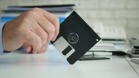 De rusteloze zakenman die ter beschikking een diskette houden maakt zenuwachtige gebaren stock videobeelden