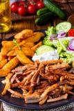 De rustieke gyroscopen plateren het groene salade en aardappelwiggen royalty-vrije stock foto's