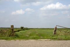 De rustieke open poort wordt overwoekerd met onkruid, blauwe hemel met wolken royalty-vrije stock afbeelding