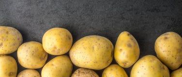 De ruwe aardappels op de donkere steen dienen het brede scherm in Stock Afbeeldingen
