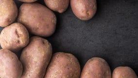 De ruwe aardappels op de donkere steen dienen horizontaal in Stock Foto