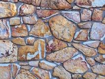 De ruwe bakstenen muur van aarde en steen kleurde natuurlijke blokken Stock Foto's