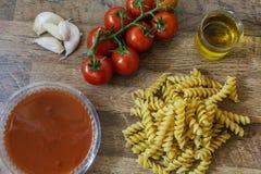 De ruwe deegwaren en de ingrediëntennoedel, kersentomaten, olijfolie, knoflook voor maken traditioneel Italiaans voedsel stock foto's
