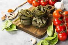 De ruwe deegwaren van tagliatelle met spinazie en ingrediënten voor het koken van kersentomaten, kruiden, knoflook, spinazie gaan Royalty-vrije Stock Afbeelding