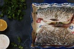 De ruwe die vis met uien en kruiden wordt gevuld wordt gevestigd in een ceramische vorm op een donkere achtergrond stock afbeeldingen
