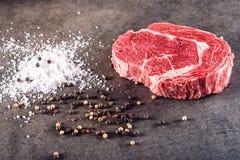 De ruwe filet van het rundvleeslapje vlees met ingrediënten zoals overzees zout en pepperon zwarte raad, beeld voor restaurant, Stock Afbeelding