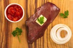 De ruwe kalfsvleeslever op houten raad met boter, ui, tomaat dobbelt en peterselie stock foto