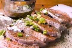 De ruwe karbonades van het Varkensvleeslendestuk op een knipsel schepen met kruiden, rozemarijn, thyme, Spaanse pepers, zout, pep royalty-vrije stock afbeeldingen