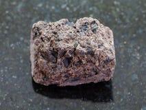de ruwe steen van het Turfgras op donkere achtergrond Stock Afbeeldingen