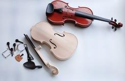 De ruwe viool en de toebehoren zetten naast voltooide viool stock fotografie