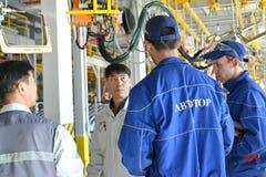 De ryska arbetarna diskuterar installation av de nya utrustningwina Arkivfoto