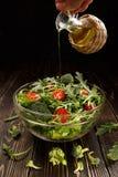 In de salade giet de plantaardige olie Stock Afbeeldingen