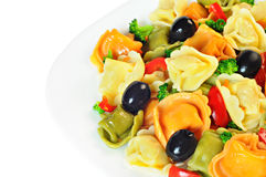 De salade maakte met tortellini, olijven, broccoli, Spaanse peper, op een plaat Stock Afbeeldingen