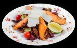 De salade met geroosterde zalm, parmezaanse kaaskaas, tomaten, mengde greens, geïsoleerde sla en kalk, stock fotografie