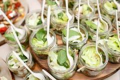 De salade met groene tomaten, doorbladeren en feta-de kaas in metselaarkruiken Royalty-vrije Stock Foto's