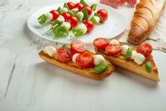 De salade van Bruschettacaprese - de kebab met tomaat, mozarella en basilicum, tomaten en Franse baguette, Italiaanse keuken en h stock afbeeldingen